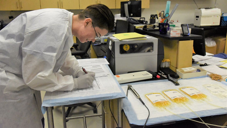Technician takes notes next to convalescent plasma samples.