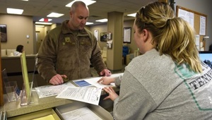Military personnel at desk assisting an Airman with paperwork