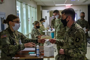 Military personnel wearing face mask checking in to receive the COVID-19 Vaccine