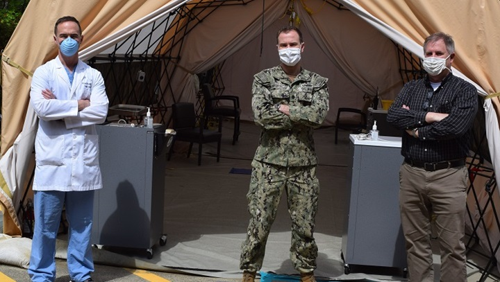 Three men standing in front of a military medical tent