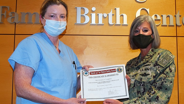 Military personnel gives nurse an award