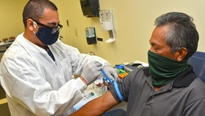 Medical technician giving a man a vaccine shot; both wearing masks