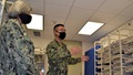 Two military personnel, wearing masks, in a supply room looking at the shelves