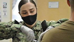 Technician wearing a mask, giving a shot to a soldier