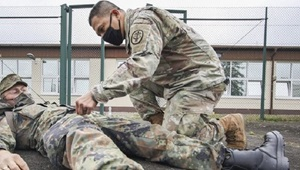 Two soldiers, one laying on the ground and the other giving him medical attention
