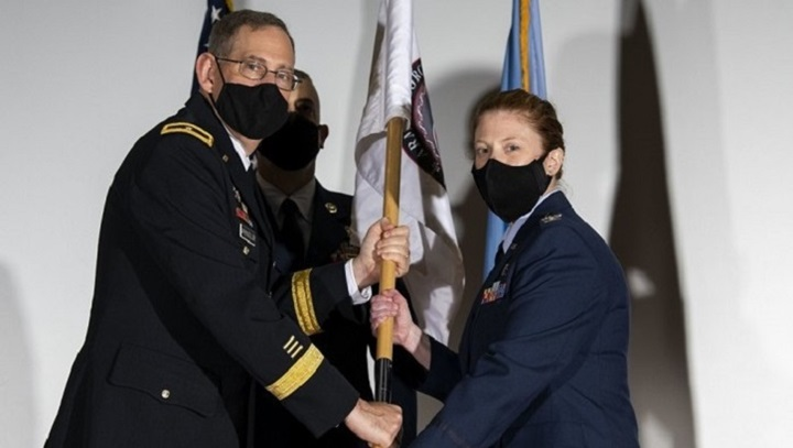 Two military personnel wearing masks, holding onto a flag