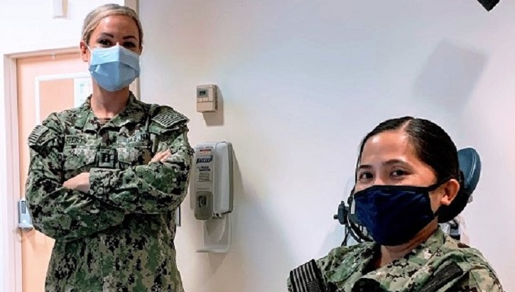 Image of two military personnel wearing masks
