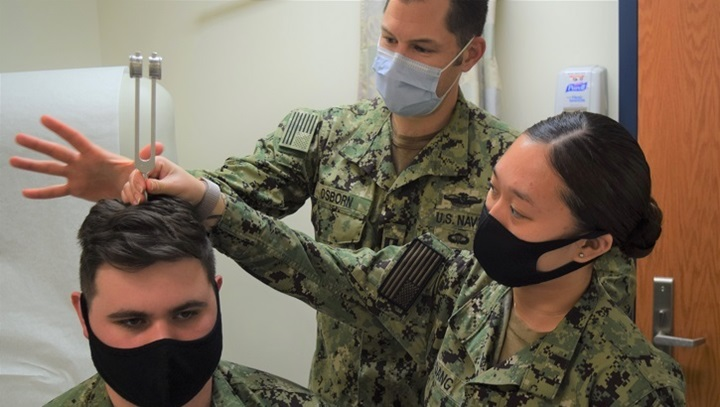 Three soldiers, wearing masks, demonstrating a hearing test