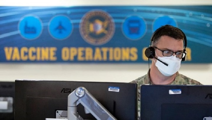 Soldier wearing mask, sitting in front of computer monitors