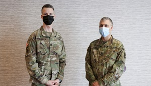 Two military personnel, wearing masks, standing against a wall