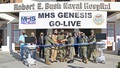 "Military personnel standing in front of hospital with sign ""MHS GENESIS GO-LIVE"""