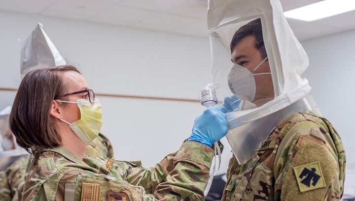 Army technician fits soldier with face mask
