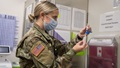 A military nurse, wearing a mask, prepares a needle for a vaccination