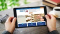 Two hands holding a tablet, which displays a new TRICARE MTF website, against a background of a wooden table.