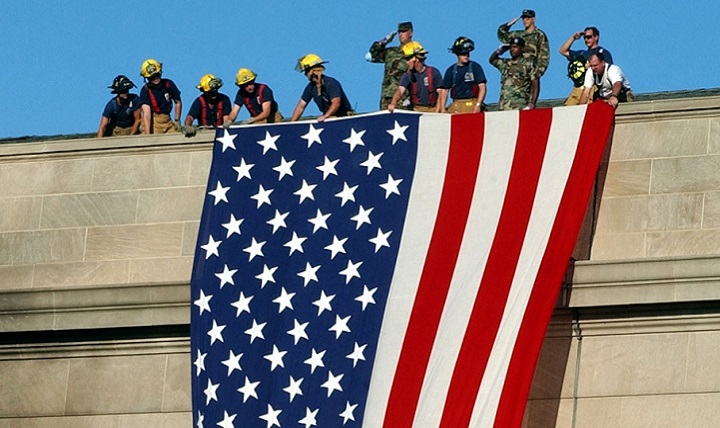 The garrison flag is hung from the still smoldering Pentagon by service members and firefighters. (DoD photo)