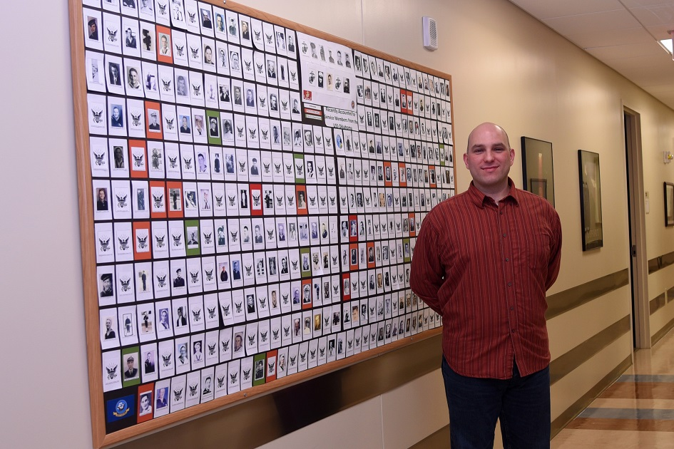 Sean Patterson, Armed Forces Medical Examiner System Department of Defense DNA Registry DNA analyst, stands in front of the USS Oklahoma Identification Board Nov. 29, 2016, at AFMES on Dover Air Force Base, Delaware. The board provides a picture for all 393 unaccounted service members from the ship. (U.S. Air Force photo/Senior Airman Ashlin Federick)