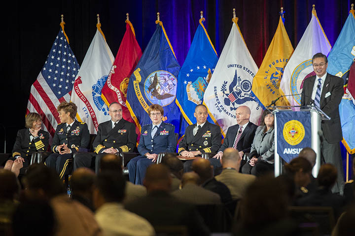 Dr. John Cho (far right), AMSUS executive director, introduces speakers (from left) Navy Vice Adm. Raquel Bono, Defense Health Agency director; Lt. Gen. Nadja West, Army surgeon general; Vice Adm. Forrest Faison III, Navy surgeon general; Lt. Gen. Dorothy Hogg,  Air Force surgeon general; Navy Rear Adm. Colin Chinn, Joint Staff surgeon, Dr. Richard Thomas, president of Uniformed Services University of the Health Sciences; and Dr. Terry Adirim, deputy assistant secretary of defense for health services policy and oversight.