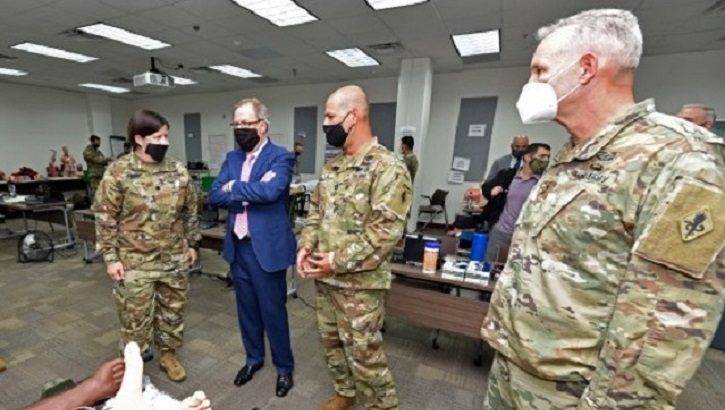 Three soldiers and Mr. McCaffery, wearing masks, talking