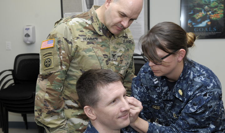 Army Col. Dean Hommer (left), a visiting instructor from Brooke Army Medical Center at Fort Sam Houston, Texas, observes as Navy nurse Lt. Rachael Wheelous (right) practices the battlefield acupuncture technique on Navy nurse Lt. Brent Pavell (center) during training at Naval Health Clinic Corpus Christi, Texas. (U.S. Navy photo by William Love)