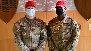 Two military personnel in masks pose for picture