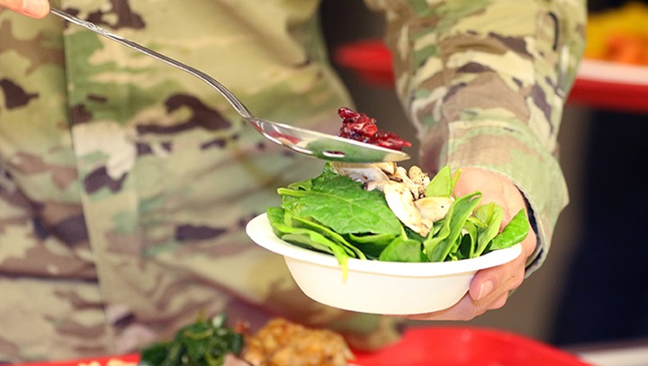Soldier holding a bowl of lettuce and vegetables