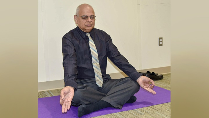 Dr. Bhagwan Bahroo, staff psychiatrist, demonstrates a deep-breathing posture as he leads a weekly yoga class for Psychiatry Continuity Service Program participants at Walter Reed National Military Medical Center. (DoD photo by Leigh Culbert)