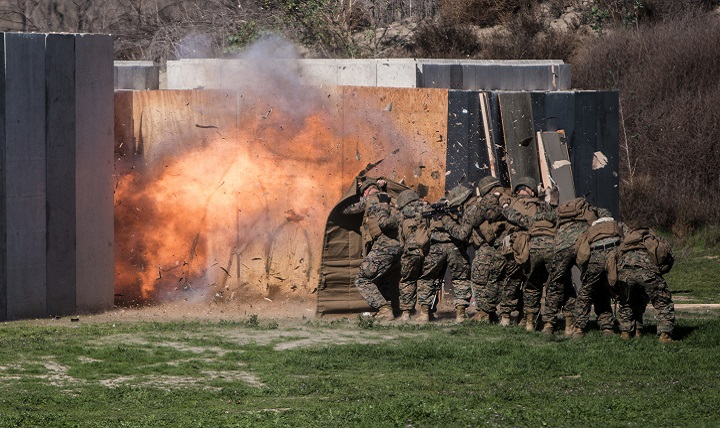 Marines shield themselves from a detonated explosive charge during a breaching exercise. Modern body armor better protects warfighters against shrapnel from explosive blasts. However, they still face the resulting blast pressure and shock wave that could cause traumatic brain injury. (U.S. Marine Corps photo by Sgt. Emmanuel Ramos)