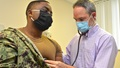 Military personnel wearing a face mask, gets his heart checked out by military heath personnel