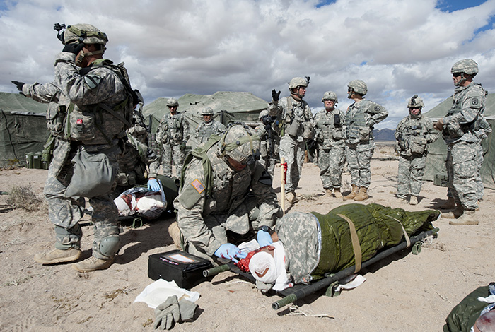 "Soldiers from the 15th Brigade Support Battalion out of Fort Hood, Texas, provide treatment to the ""wounded"" during a mass casualty exercise, March 2, 2015. The training, taking place on Fort Irwin, California, is part of a National Training Center rotation scenario testing their ability to perform under a simulated combat environment. (Photo Credit: G. A. Volb)"