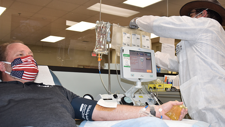 Image of man wearing mask and giving blood