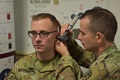Army audiologist Maj. William Gottlick, (right) Lyster Army Health Clinic, Fort Rucker, Alabama, conducts an otoscopic exam during an annual hearing test. (Army photo by Jennifer Stripling)