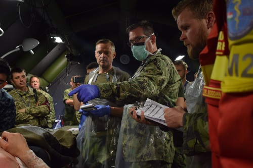 Navy Cmdr. Corey Gustafson (center right) and Capt. Martin Stenerös (center left), Swedish armed forces, participate in a multinational medical drill, Cincu Military Base, Romania, during exercise Vigorous Warrior 19. Vigorous Warrior 19 is NATO's largest-ever military medical exercise, uniting more than 2,500 participants from 39 countries to exercise experimental doctrinal concepts and test their medical assets together in a dynamic, multinational environment. (U.S. Air Force photo by 1st Lt. Andrew Layton).