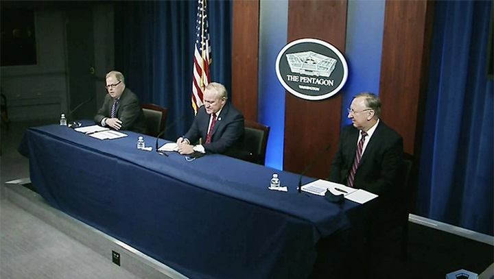 Three men sit at blue table with American Flag and Pentagon symbol behind them.