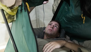 Image of soldier lying down, looking at his phone