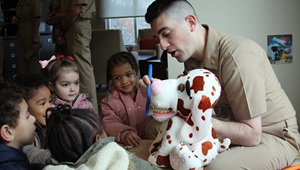 Military health personnel, sitting in front of a group of children, showing them how to brush their teeth using a stuffed animal