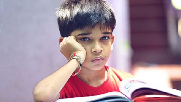 a young boy looking sad while reading a book