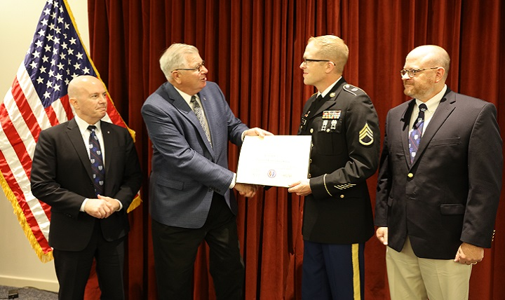 Uniformed Services University of the Health Sciences President, Dr. Richard Thomas (left) and USU College of Allied Health Sciences Dean Dr. Mitchell Seal (right) watch as the former university Senior Vice President Dr. Patrick Sculley presents Army Staff Sgt. Robert Eccles with an Associate of Science degree in Health Sciences.  Eccles is the first CAHS degree recipient.  (DoD photo by Sharon Holland)