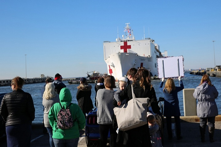 Family and friends of crew members aboard Military Sealift Command's hospital ship USNS Comfort wait as the ship pulls into Naval Station Norfolk, Dec. 18. Comfort returned to Virginia after completing its 11-week medical support mission to South and Central America, part of U.S. Southern Command's Operation Enduring Promise initiative. (U.S. Navy photograph by Brian Suriani)
