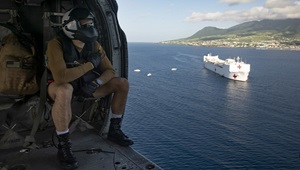 "Navy Naval Aircrewman (Helicopter) 2nd Class Benjamin Lazarus flies in an MH-60S Seahawk assigned to the ""Dragon Whales"" of Helicopter Sea Combat Squadron 28, as it transports supplies from the hospital ship USNS Comfort for a temporary medical treatment site in Basseterre, St. Kitts and Nevis. (U.S. Navy photo by Mass Communication Specialist 2nd Class Morgan K. Nall)"