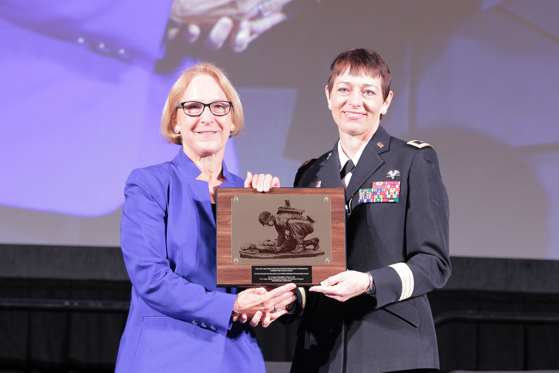 Major General Barbara R. Holcomb, commanding general of the U.S. Army Medical Research and Materiel Command, presented Connie S. Schmaljohn, Ph.D. and her team of military and civilian scientists from the U.S. Army Medical Research Institute of Infectious Disease the 2017 Team Research Accomplishment (Military), in the category of Infectious Disease, on Aug. 28 at the Military Health System (MHS) Research Symposium. The team received honorable mention for the successful development and human clinical testing of a state-of-the-art DNA vaccine to prevent hemorrhagic fever with renal syndrome.