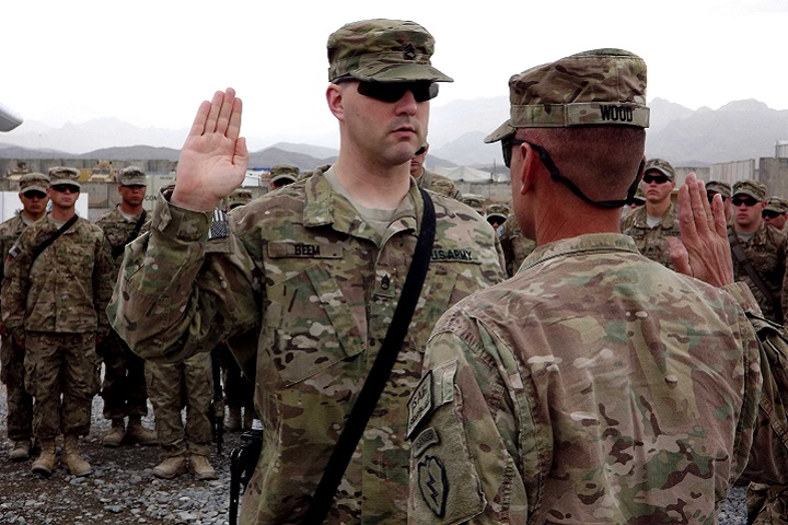 Army Col. Todd R. Wood, commander of the 1st Stryker Brigade Combat Team, 25th Infantry Division, administers the oath of re-enlistment to Army Staff Sgt. Brian Beem, left, then a cavalry scout assigned to the 5th Squadron, 1st Cavalry Regiment, at Forward Operating Base Frontenac, Afghanistan, Nov. 9, 2011. Beem is a single-leg amputee who was able to continue to serve despite his injury. He lost his leg after an improvised explosive device detonated during his 2006 deployment to Iraq. (U.S. Army photo by Sgt. Thomas Duval)