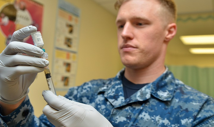 Navy Petty Officer 3rd Class Brett Friebel prepares a flu shot for a patient at Naval Branch Health Clinic Mayport's immunizations clinic. (U.S. Navy photo by Jacob Sippel)