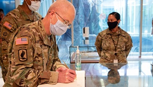 Military Personnel wearing a face mask signing a book