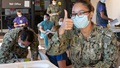 Several military personnel, wearing masks, filling out paperwork. One woman is giving the thumbs up sign