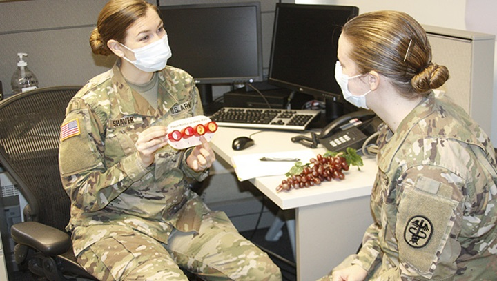 Military health personnel wearing face mask while discussing food options