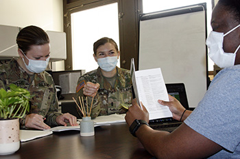 Military health personnel wearing face masks receiving instructions