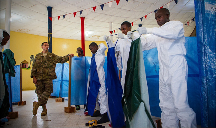 U.S. Air Force Senior Airman Joshua Douglass, left, an aerospace medical technician, watches as Liberian health care workers properly put on their personal protective equipment as part response by the Defense Department operation to provide logistics, training and engineering support during the Ebola virus outbreak. (U.S. Army photo by Staff Sgt. Terrance D. Rhodes)