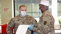 Military health personnel wearing face mask discussing food options