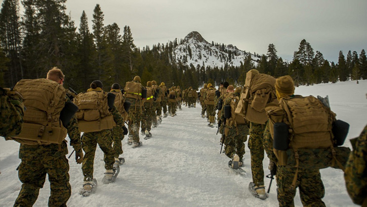 Group of Marines, snowshoeing through the snow