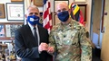 Two men in masks; one a military soldier, and the other wearing a suit.
